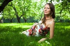 La belle femme se trouve sur l'herbe Image stock