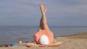 La belle femme se trouve sur la plage et fait des jambes d'échauffement clips vidéos