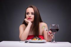 La belle femme seul mangeant avec du vin Photographie stock libre de droits