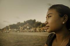 La belle femme seule asiatique regardant à l'infini a perdu dans ses pensées tristes et séance réfléchie sur la plage de sable photographie stock