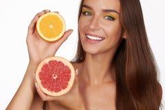 La belle femme sexy de brune avec l'agrume sur un fond blanc, nourriture saine, nourriture savoureuse, régime organique, sourient images libres de droits