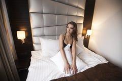 La belle femme sexy de brune s'asseyent dans le lit Image stock
