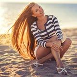 La belle femme sexy est habillée dans un gilet dépouillé par mer se repose sur les rêves de bord de la mer Photo libre de droits