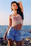 La belle femme sexy porte un dessus avec des shorts de jeans et plage de pose Image libre de droits