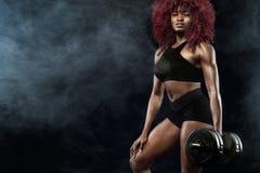 La belle femme sportive avec des haltères fait la forme physique s'exerçant au fond noir pour rester convenable Image libre de droits