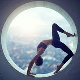 La belle femme sportive de yogi d'ajustement pratique l'asana Eka Pada Urdhva Dhanurasana de yoga dans une fenêtre ronde photo stock