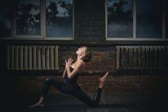 La belle femme sportive de yogini d'ajustement pratique l'asana Ashva Sanchalasana - pose équestre de yoga dans le hall foncé photos libres de droits