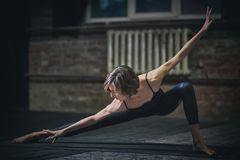 La belle femme sportive de yogini d'ajustement pratique l'asana de yoga dans le hall foncé image libre de droits