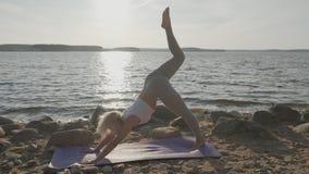 La belle femme sportive faisant des exercices de matin sur le bord de la mer Plage et lever de soleil sur le fond clips vidéos
