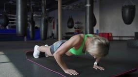 La belle femme sportive fait des pousées en tant qu'élément de sa forme physique croisée, routine de formation de gymnase de body banque de vidéos