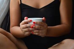 La belle femme tient une tasse de café dans des ses mains photo libre de droits