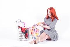 La belle femme tire des sacs de cadeau d'écharpe de mesure image stock