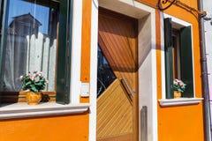 La belle fenêtre orange avec le pot fleurit en île de Burano (Venise, Italie) Photo stock