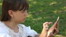 La belle fille ? l'aide d'un smartphone ?crit une lettre sur un banc dans un beau parc vert Mouvement lent la fille d'adolescent  clips vidéos