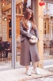 La belle fille à la mode dans le pantalon et des espadrilles gris de manteau ferme le sac quittant le restaurant Photographie stock