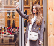La belle fille à la mode dans les pantalons et des espadrilles gris de manteau avec un sac à main à la mode fait le smartphone de Photos libres de droits