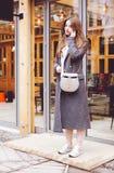La belle fille à la mode dans les pantalons et des espadrilles gris de manteau parle du smartphone quittant le restaurant Image libre de droits