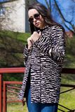La belle fille élégante marche en parc dans des lunettes de soleil en premier ressort un jour lumineux ensoleillé Photo stock