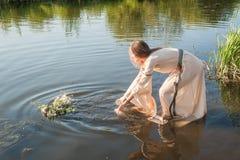 La belle fille abaisse la guirlande dans l'eau image stock