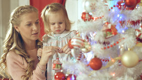 La belle fille accroche la boule de Noël sur l'arbre avec sa mère Photographie stock