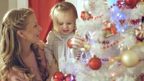 La belle fille accroche la boule de Noël sur l'arbre avec sa mère Images stock