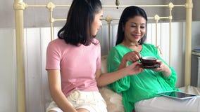 La belle fille apportent le café chaud à sa mère dans la chambre à coucher Photos stock