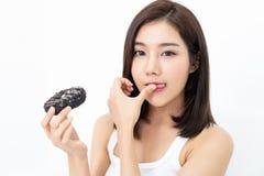 La belle fille asiatique a plaisir à manger un beignet avec du chocolat et à sucer son doigt sur d'isolement sur le fond blanc images stock