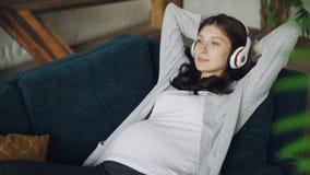 La belle fille attendant la mère écoute les écouteurs de port de musique et détend sur le sofa à la maison appréciant le repos et banque de vidéos