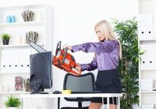 La belle fille au bureau coupe le moniteur avec une tronçonneuse Image stock