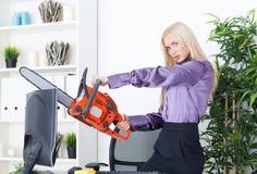 La belle fille au bureau coupe le moniteur avec une tronçonneuse Photographie stock