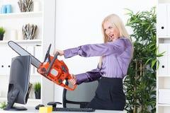 La belle fille au bureau coupe le moniteur avec une tronçonneuse Photo stock