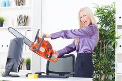 La belle fille au bureau coupe le moniteur avec une tronçonneuse Images libres de droits