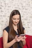La belle fille aux cheveux longs parle au café par le téléphone Photos stock