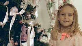 La belle fille aux yeux bleus accroche un jouet fait maison de Noël sur l'arbre de Noël Image stock
