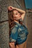 La belle fille avec de longs cheveux et dans une veste de denim se tient près du mur pendant l'été photos libres de droits
