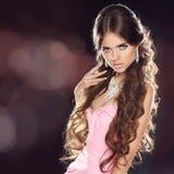 La belle fille avec de longs cheveux onduleux d'isolement sur le bokeh s'allume de retour Photos libres de droits