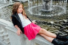 La belle fille avec de longs cheveux se trouve dessus de retour sur la balustrade luxueuse dans la fontaine du ` s de ville en pa Photos stock