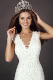 La belle fille avec de longs cheveux utilise la robe et la couronne luxueuses Photo stock