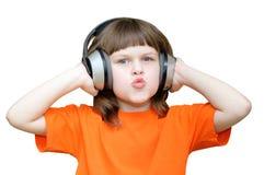 La belle fille avec des écouteurs sur sa tête a plié ses lèvres dans a Images libres de droits