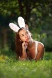 La belle fille avec des oreilles de lapin se trouve sur une herbe Photographie stock libre de droits
