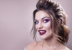 La belle fille avec des yeux bleus, émotion d'une chevelure et belle brune avec la langue sur un fond rose photo libre de droits