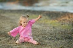 La belle fille avec la trisomie 21 montre comment un oiseau vole sur la plage Photographie stock libre de droits