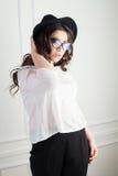 La belle fille avec le chapeau et les verres dans le studio courbe la coiffure photo stock