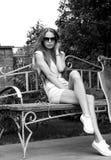 La belle fille avec le longboard s'assied sur le banc dedans Photo stock
