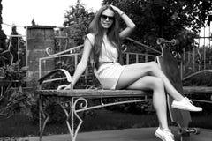 La belle fille avec le longboard s'assied sur le banc dedans photo libre de droits