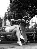 La belle fille avec le longboard s'assied sur le banc dedans Photographie stock