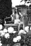 La belle fille avec le longboard s'assied sur le banc dedans Image stock