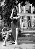 La belle fille avec le longboard s'assied sur le banc dedans Photos libres de droits