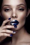 La belle fille avec le maquillage d'art, les lèvres foncées de scintillement conçoivent et des ongles manucurés Visage de beauté images libres de droits