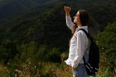 La belle fille avec le sac à dos rencontre le lever de soleil dans une forêt Photos stock